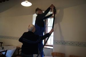 In der Zwischenzeit werden von Peter Huber und Walter Lauer die Löcher in der Wand für die Vorhangstangen gebohrt.